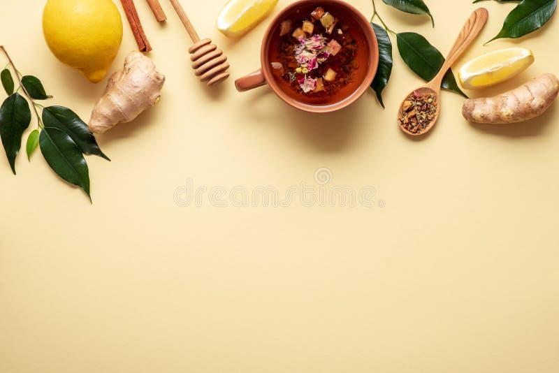 Accesorios de la taza de té y del té en el fondo amarillo, frontera superior con la taza de té con el té orgánico, cuchara del té fotos de archivo libres de regalías