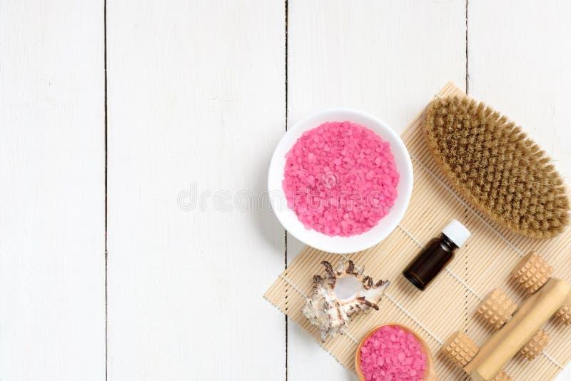 Accesorios del balneario con la sal de baño y el aceite color de rosa en la tabla de madera Maqueta de la bandera con el espacio  imagenes de archivo