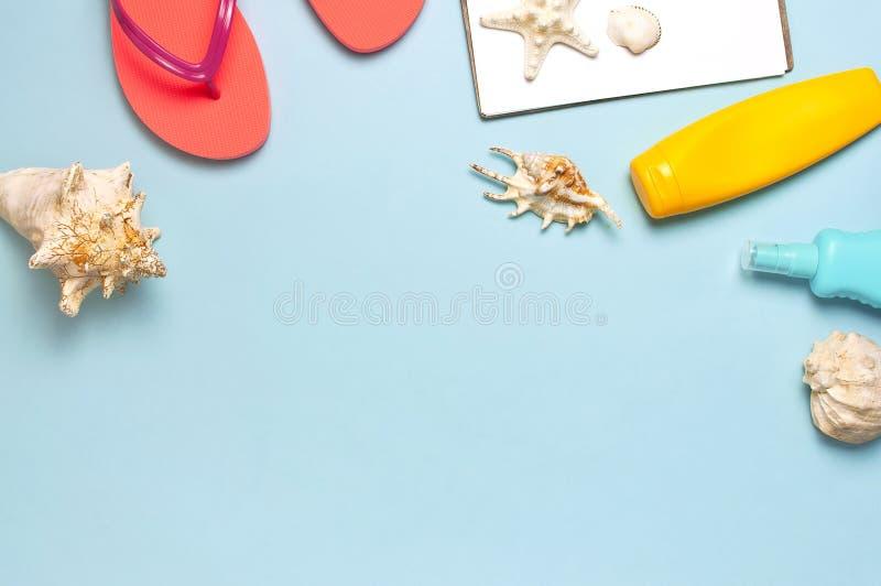 Accesorios del mar de la playa del verano Chancletas coralinas, c?scaras, estrellas de mar, botella amarilla de la protecci?n sol foto de archivo