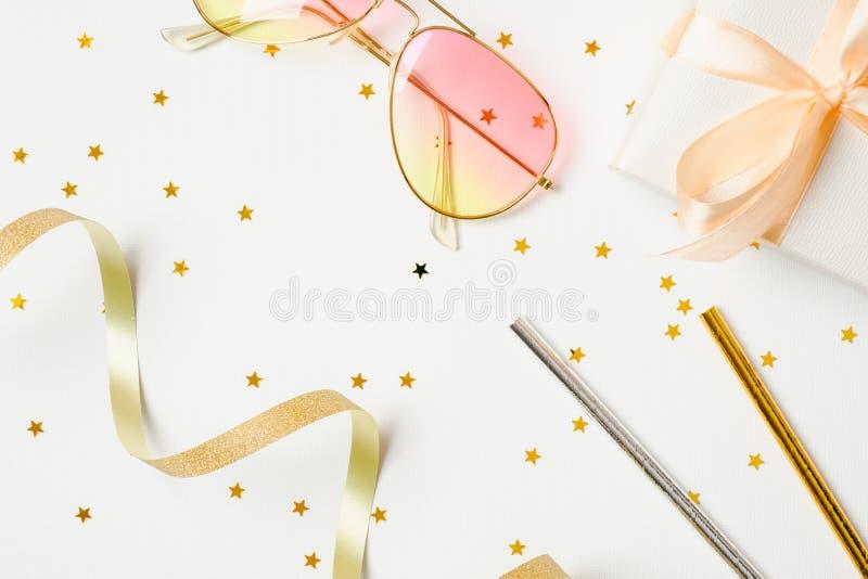 Accesorios del partido del verano sobre el fondo blanco Materia festiva, estrellas del confeti, cinta, gafas de sol, caja de rega imagenes de archivo