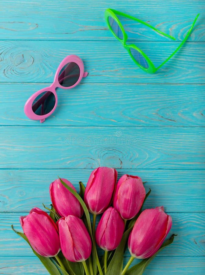 Accesorios del ` s de las mujeres - gafas de sol y ramo de tulipanes rosados en a fotos de archivo