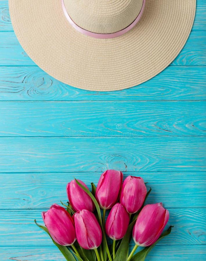 Accesorios del ` s de las mujeres - sombrero y ramo de tulipanes rosados en un de madera imagenes de archivo