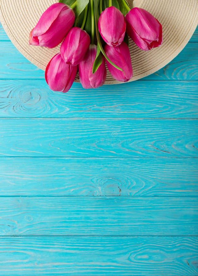Accesorios del ` s de las mujeres - sombrero y ramo de tulipanes rosados en un de madera foto de archivo libre de regalías
