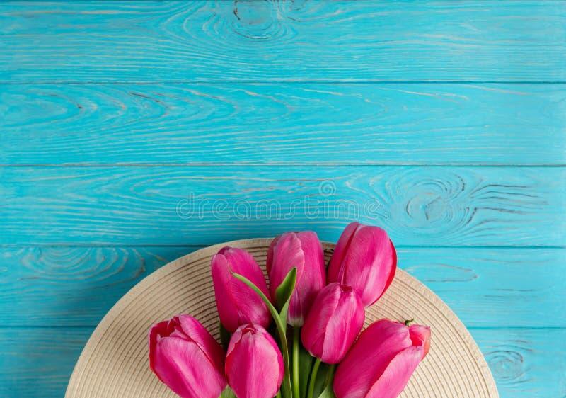 Accesorios del ` s de las mujeres - sombrero y ramo de tulipanes rosados en un de madera fotos de archivo