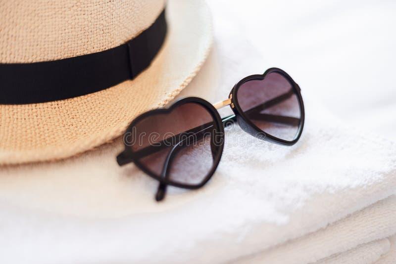 Accesorios del verano para la playa Gafas de sol en forma de corazón, sombrero de paja hecho punto elegante y toallas blancas Con foto de archivo libre de regalías