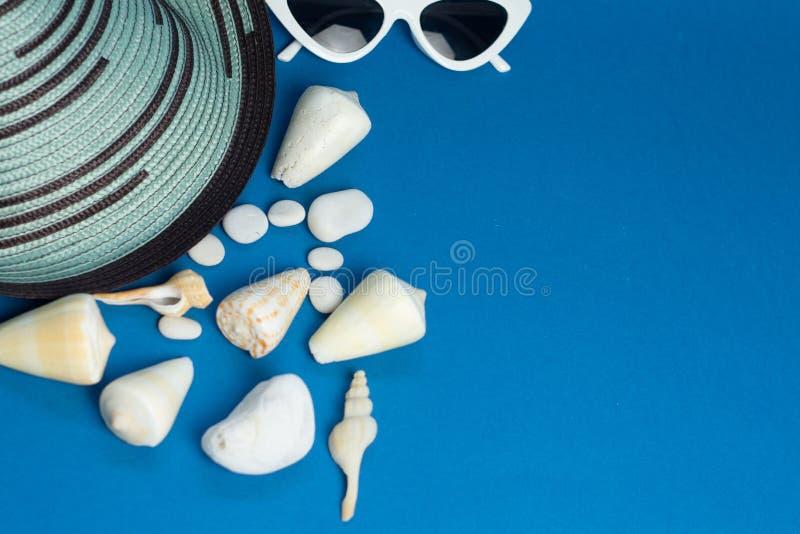 Accesorios del verano, sombrero, cáscaras, vidrios de sol en un fondo azul brillante El concepto de vacaciones del mar del verano imagen de archivo