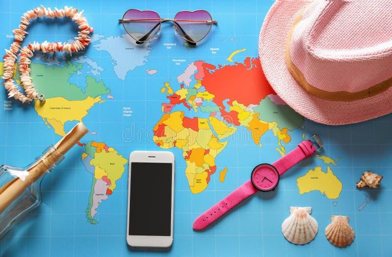 Accesorios femeninos con el teléfono móvil en mapa del mundo imagen de archivo