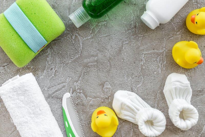 Accesorios, juguetes, toalla y ropa del cuidado del bebé en mofa gris de la opinión superior del fondo para arriba fotografía de archivo libre de regalías