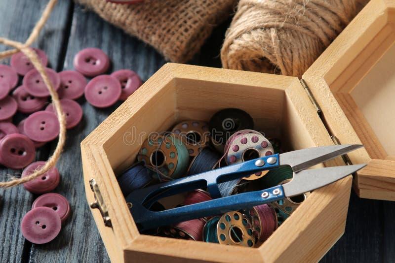 Accesorios para coser y la costura ataúd con las bobinas y el primer de las tijeras en un fondo de madera azul foto de archivo