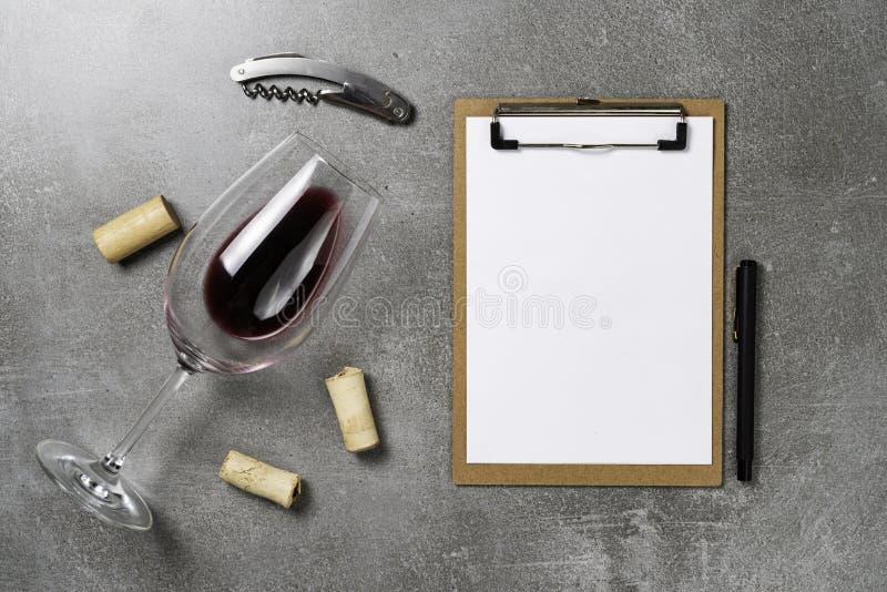 Accesorios para la enolog?a Taza con el vino en fondo y la libreta concretos Copie el espacio imagen de archivo