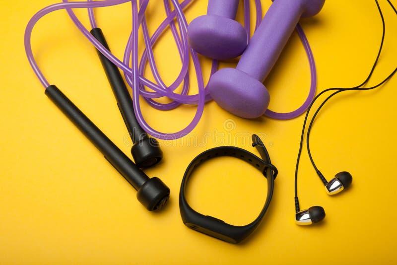 Accesorios para los deportes y atletismo, pesas de gimnasia y una cuerda que salta con una pulsera de la aptitud imagen de archivo