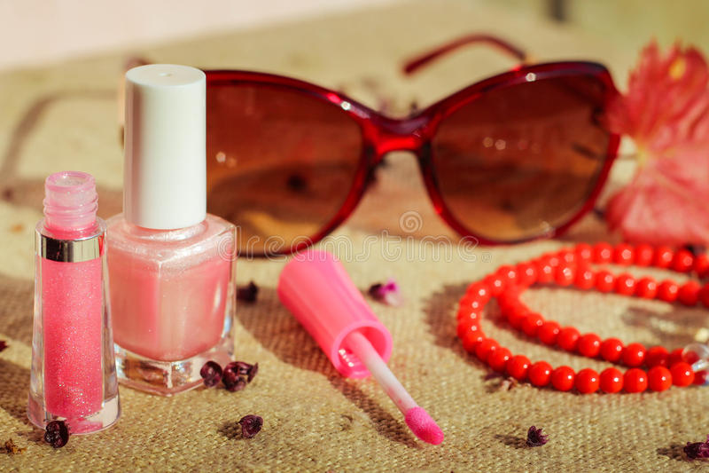 Accesorios para mujer: gafas de sol, lustre del labio, esmalte de uñas, gotas fotos de archivo