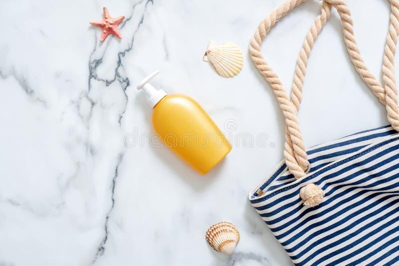 Accesorios puestos planos de la playa Botella de la crema de la protección solar, bolso rayado de la playa, conchas marinas en el fotografía de archivo
