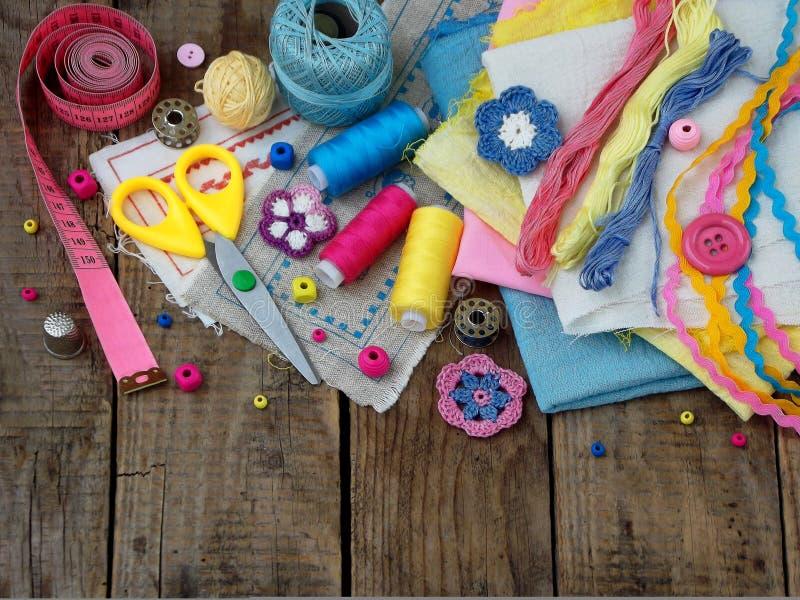 Accesorios rosados, amarillos y azules para la costura en fondo de madera El hacer punto, bordado, cosiendo Pequeña empresa Renta imágenes de archivo libres de regalías