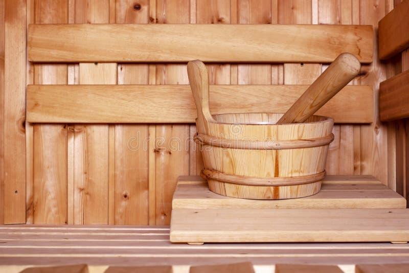 Accesorios, un cubo de madera y una cucharón, en un baño ruso tradicional o una sauna finlandesa, en un interior acogedor con nat fotografía de archivo