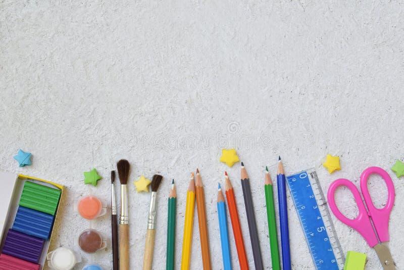 Accesorios y fuentes de la escuela: lápices, marcadores, pintura, plumas, regla en un fondo ligero De nuevo a concepto de la escu imágenes de archivo libres de regalías