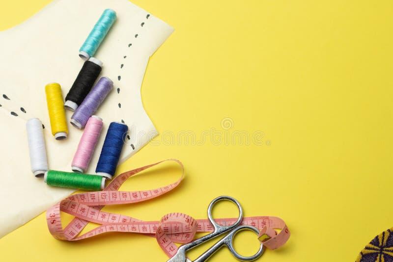Accesorios y tela de costura en un fondo del yelow Hilos de coser, pernos, modelo y centímetro de costura Para coser en casa tapa foto de archivo