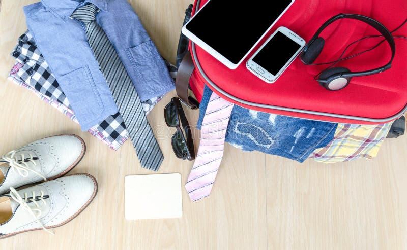 accesorios y traje del viaje en el piso de madera, mezclilla, camisa, zapatos foto de archivo libre de regalías