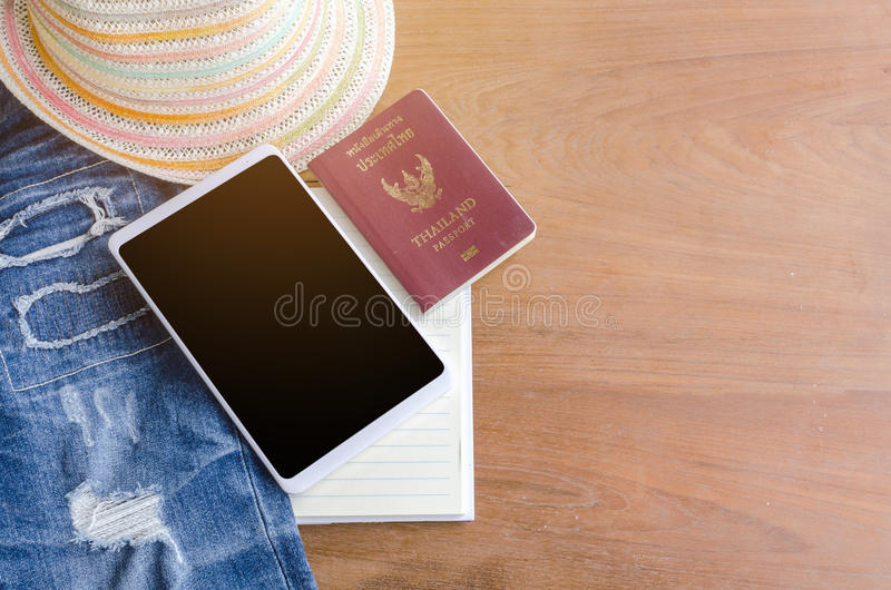 Accesorios y traje del viaje en el piso de madera, tableta, pasaporte, imagen de archivo libre de regalías