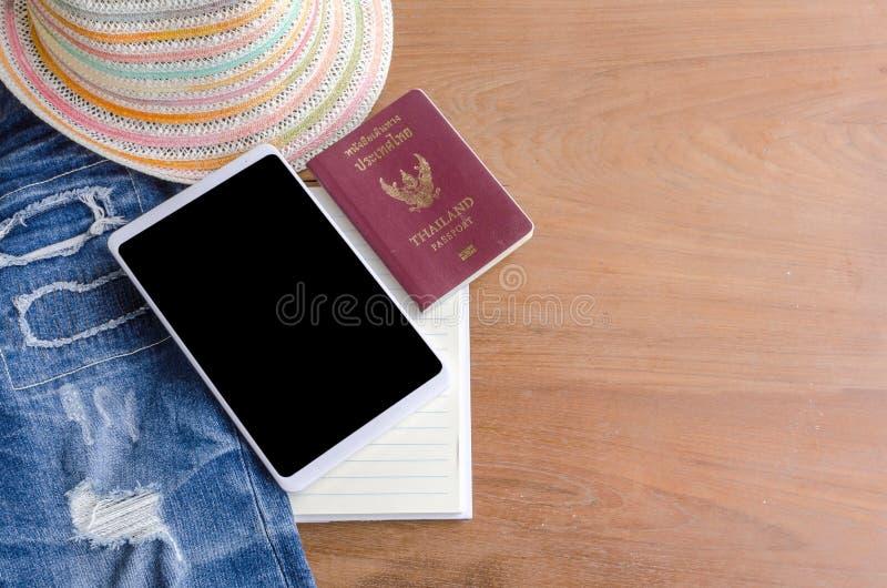 Accesorios y traje del viaje en el piso de madera, tableta, pasaporte, foto de archivo libre de regalías