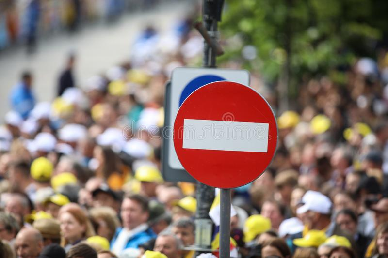 Access denied road sign with a large mass of people in the background - social or mass control.  royalty free stock images