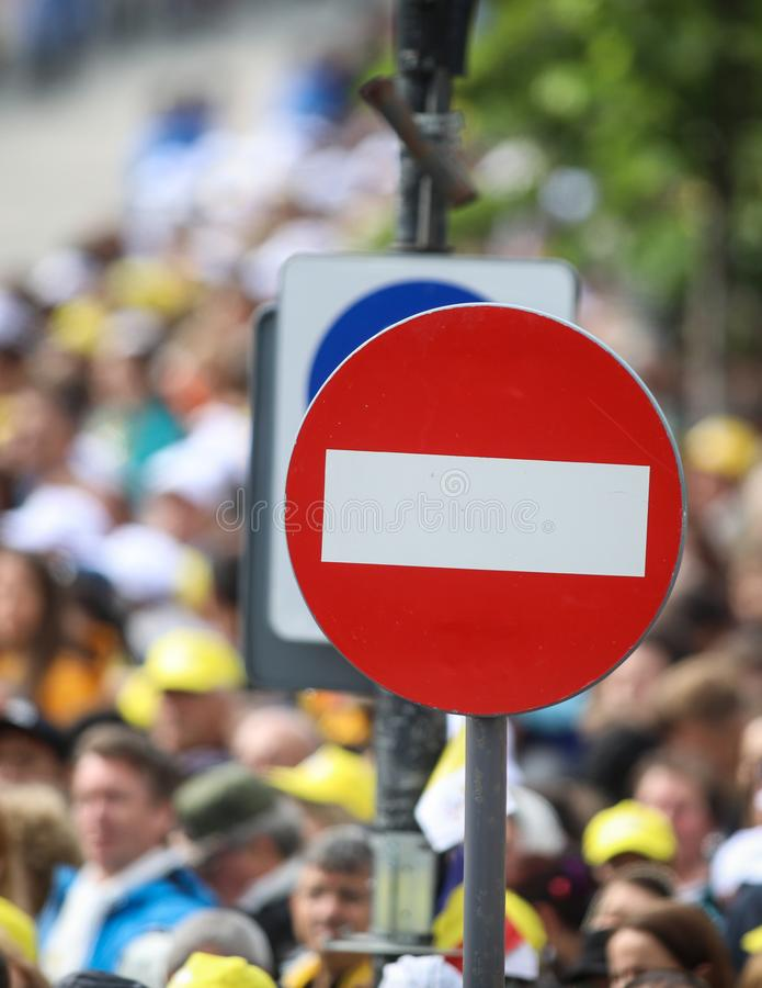 Access denied road sign with a large mass of people in the background - social or mass control.  royalty free stock photography