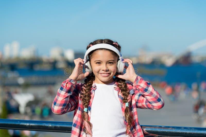 Access a milioni di canzoni Migliori apps di musica che meritano la a per ascoltare Il bambino della ragazza ascolta musica all'a immagine stock