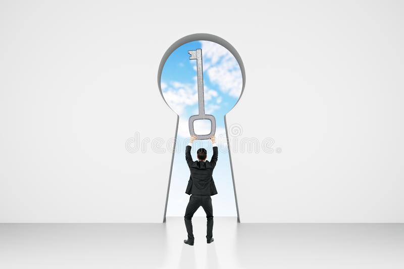 Access and opportunity concept. Back view of young businessman in abstract white concrete interior with keyhole window and sky view. Access and opportunity royalty free stock photography
