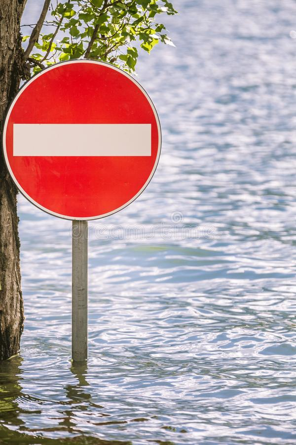 Access prohibition road sign partially submerged in a flood. Red disk with white horizontal stripe. Flooding due to very strong climatic perturbations royalty free stock photo