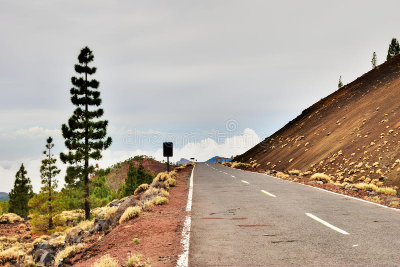 The Access Road To Teide National Park, Tenerife. A view of the deserted tarred road leading through rich red volcanic soils to the Teide National Park, Tenerife royalty free stock photography