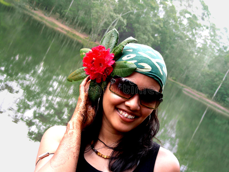 Accessarised Babe. An Indian babe using flower as a hair accessory standing by the lake royalty free stock photography