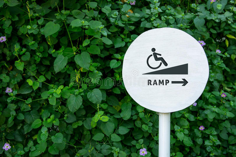 Accessibility in city public park, Sign board of Ramp for Disabled people or handicapped, Natural green leaf as backdrop wall stock photo