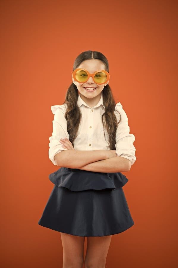 Accessoire beaucoup trop design pour décoller Petit enfant souriant dans un accessoire fantaisiste sur fond orange Bonne fille au photo stock