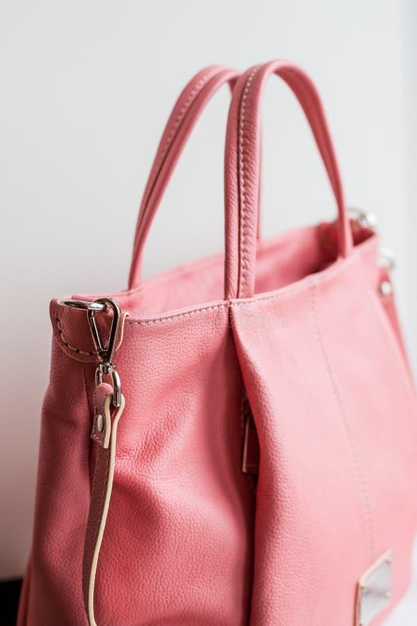 Accessoires élégants du ` s de femmes Le sac à main des belles femmes de couleur de corail vivante sur un fond blanc Rose-clair,  photo libre de droits