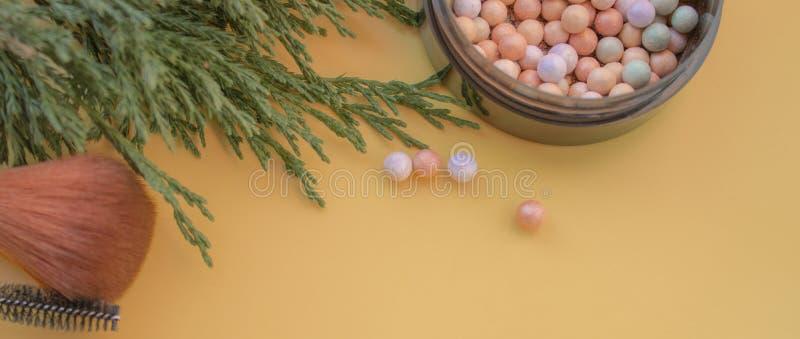 Accessoires cosmétiques Balayez, rougissez, le rouge à lèvres, branche verte sur un jaune, fond crème image stock