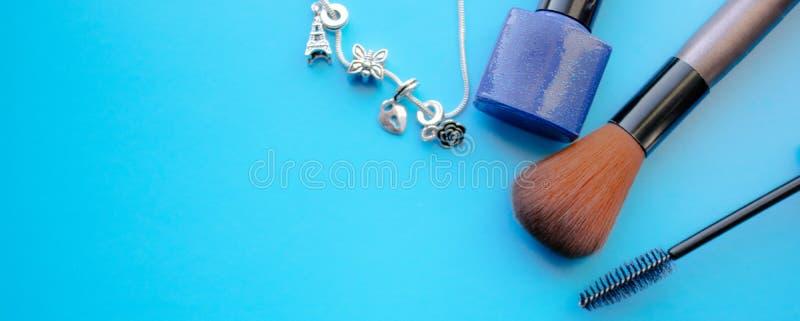 Accessoires cosmétiques La brosse pour rougissent, le pinceau, vernis à ongles sur un fond bleu image libre de droits