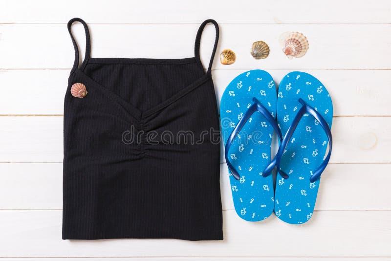 Accessoires d'été avec le T-shirt, les coquillages et les bellâtres de secousse sur la configuration plate en bois blanche de vue photo stock
