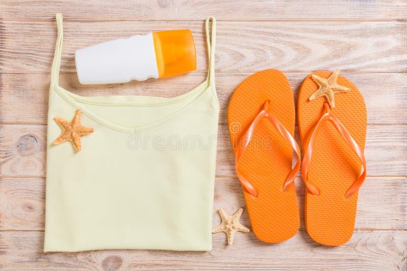 Accessoires d'été avec le T-shirt, les coquillages et les bellâtres de secousse sur la configuration plate en bois de vue supérie images stock