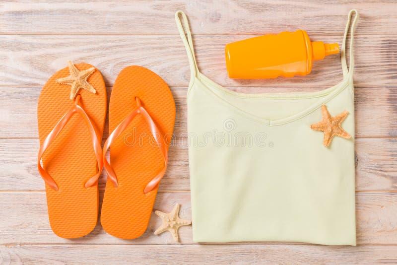 Accessoires d'été avec le T-shirt, les coquillages et les bellâtres de secousse sur la configuration plate en bois de vue supérie image stock