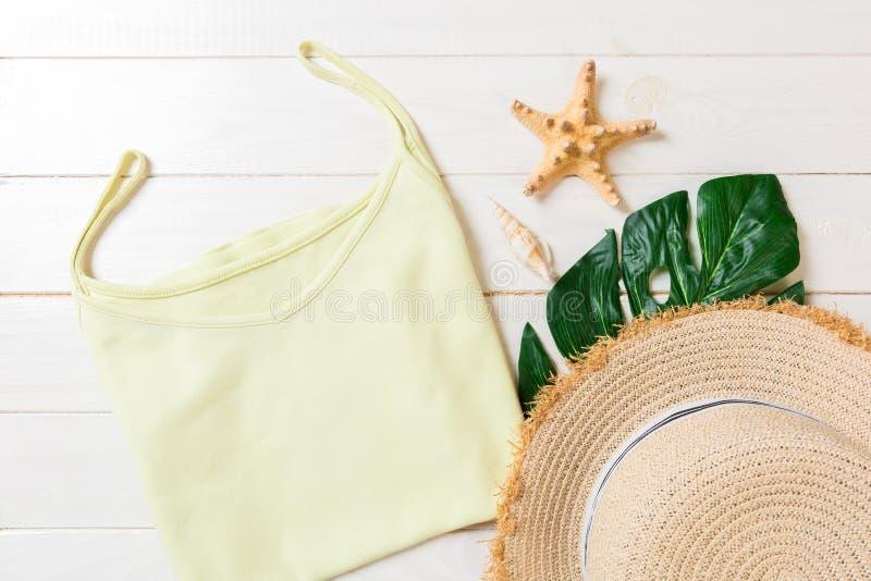 Accessoires d'été avec le T-shirt, les coquillages et le chapeau de paille sur la configuration plate en bois blanche de vue supé photographie stock libre de droits