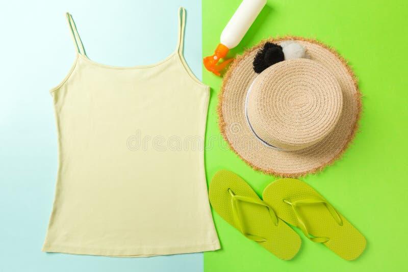 Accessoires d'été avec le T-shirt, les coquillages, la bouteille de protection solaire et le chapeau de paille sur la configurati photographie stock