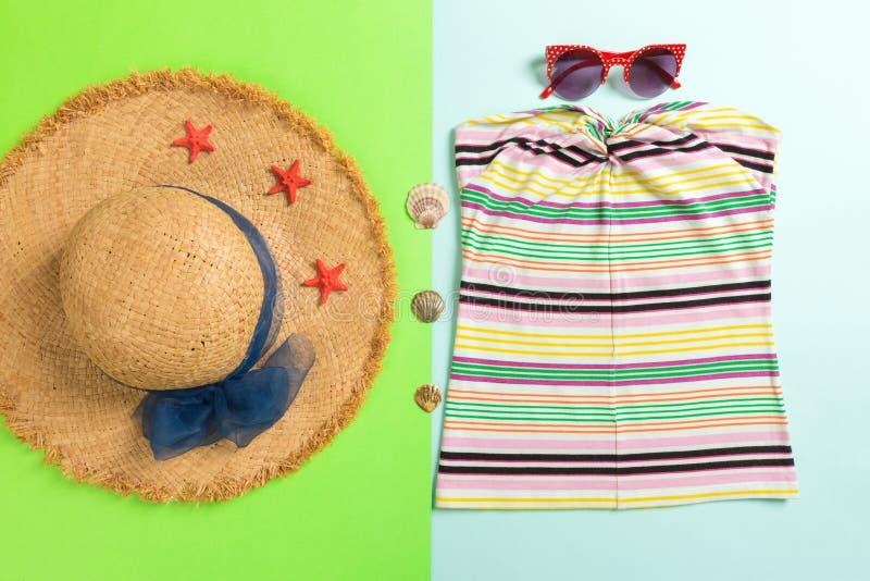 Accessoires d'été avec le T-shirt, les coquillages, les lunettes de soleil et le chapeau de paille sur la configuration plate ble photos stock