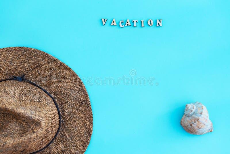 Accessoires d'été, chapeau, coquille, avec des vacances de mot dans les lettres sur un fond bleu Le concept des vacances de mer d photos libres de droits