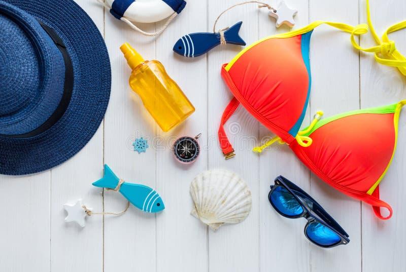 Accessoires d'été pour des vacances : chapeau de paille, boussole, coquilles, boucles d'oreille, maillot de bain, verres de solei photos stock