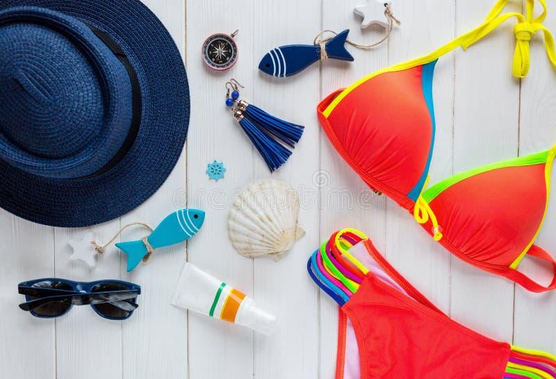 Accessoires d'été pour des vacances : chapeau de paille, boussole, coquilles, boucles d'oreille, maillot de bain, verres de solei photo stock