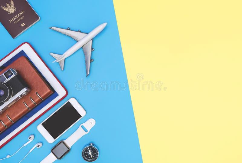Accessoires d'objets de voyage sur le fond jaune bleu avec la caméra et l'avion de passeport image stock