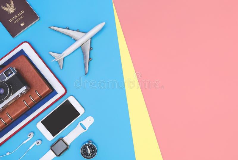 Accessoires d'objets de voyage sur le fond rose jaune bleu avec la cam?ra et l'avion de passeport photographie stock