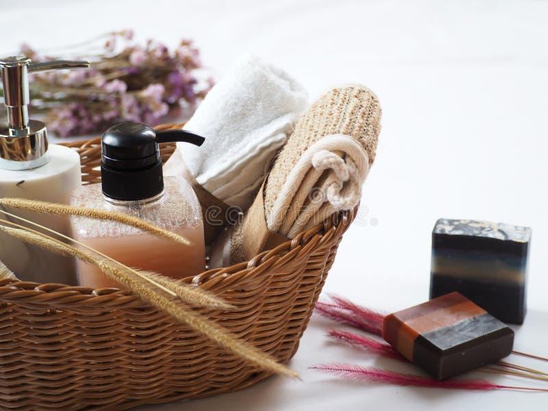 Accessoires de bain dans la corbeille, savon naturel fait maison avec décoration fleurie sur fond blanc image libre de droits