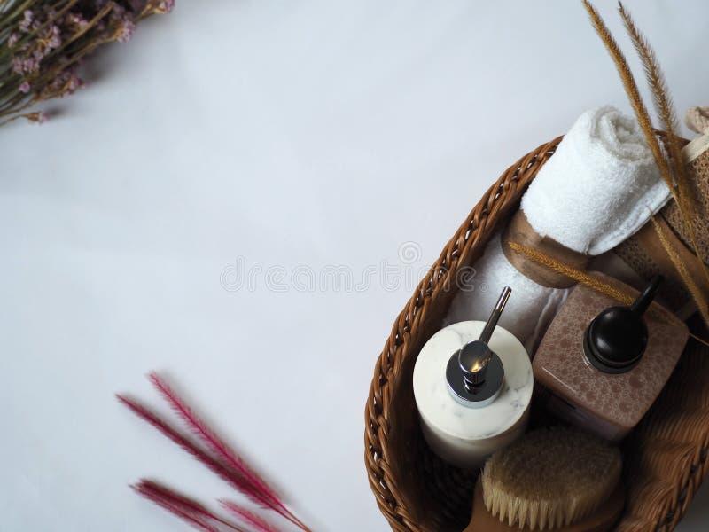 Accessoires de bain dans le panier avec décoration fleurie sur fond blanc photographie stock libre de droits