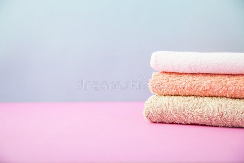 Accessoires de Bath - les serviettes se sont pliées, empilé sur une lumière, un fond bleu et rose lumineux le concept de s'occupe photo libre de droits
